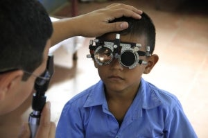 A child with a phoropter has his eyes checked by an optometrist vision care specialist