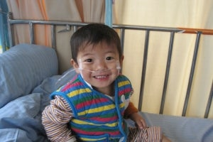 A child smiles as he sits on a hospital bed after a successful congenital heart disease surgery in China